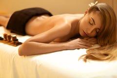 Steinmassage auf Weiß Blondine erhält Erholungs-Behandlung im Badekurort-Salon Wellne Stockbilder