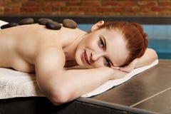 Steinmassage, Frau, die eine Warmsteinmassage erhält Lizenzfreie Stockbilder