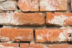 Steinmauern von roten Backsteinen mit Spuren des zerbröckelnden Gipses Stockfotos