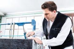 Steinmetz, der mit Druckluft am Grabstein arbeitet Stockbild