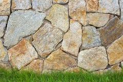 Steinmetzarbeithintergrund mit grünem Gras Stockfoto