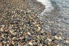 Steinmittelgroße Kiesel der seeküste wuschen sich mit Wasser lizenzfreies stockbild