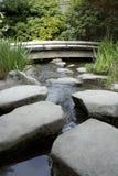 Steinpfad und hölzerne Brücke in einem Garten stockbild