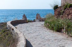Steinpflasterungsweg entlang felsiger Küste. Stockfoto