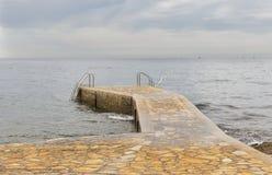 Steinpier mit Leitern für das Schwimmen an einem regnerischen Tag Lizenzfreies Stockfoto