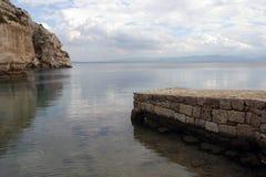 Steinpier und Felsen auf Meer lizenzfreie stockfotos