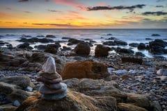 Steinpyramide und Sonnenuntergang am Strand Lizenzfreie Stockfotografie