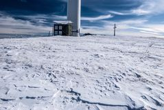 Steinriegel hilli in winter Fischbacher Alpen in Styria. Steinriegel hill with snow, small cross and bigger wind turbine on Stuhleck mountain ridge of stock photo
