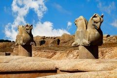 Steinsäuleskulptur eines Greifs in Persepolis gegen einen blauen Himmel mit Wolken Das Siegsymbol der alten Achaemenid-Stämme Stockbild