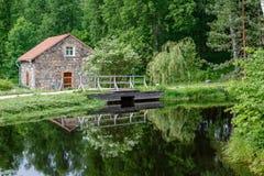 Steinscheune und eine Holzbrücke Stockbild