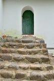 Steinschritte und alte Tür im weißen Gebäude Stockfotos