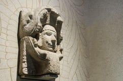 Steinskulptur des Kopfes eines Mannes innerhalb einer Schlange von kann Lizenzfreie Stockfotos