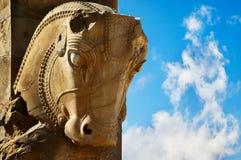 Steinskulptur eines Pferds in Persepolis gegen einen blauen Himmel mit Wolken Das Siegsymbol des alten Achaemenid-Königreiches Lizenzfreie Stockbilder