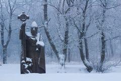 Steinstatue Heiliges Kilian im schneebedeckten Wald Stockfotografie