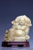 Steinstatue von Buddha auf einem hölzernen Stand Stockbilder