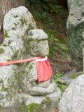 Steinstatus mit rotem Stoff Stockfotos