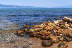Steinstrand- und Seeuferhintergrund Stockfoto