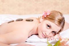Steintherapiemassage: die junge attraktive blonde Frau, die den Spaß genießt Badekurortverfahren hat, entsteinen Therapiemassage  Stockfoto