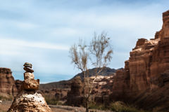Steintotem auf einem Hintergrund von roten Felsen und von Himmel mit Wolken Lizenzfreies Stockbild