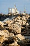 Steinverdammung am Rand des Meeres, das zu eine Fabrik führt Stockfotografie