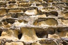Steinwand-Abnutzungs-Lochmuster-Motivbeschaffenheits-Designhintergrund Lizenzfreies Stockfoto