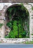 Steinwand alten Torbogens Roms mit wachsendem Efeu, Hintergrundkonzept stockbild