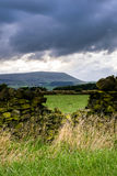 Steinwand auf dem Bauernhof mit Pendle-Hügel im Abstand auf bewölkter SU stockfotografie
