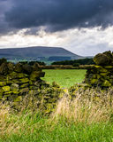 Steinwand auf dem Bauernhof mit Pendle-Hügel im Abstand am bewölkten Sommernachmittag Stockfotografie