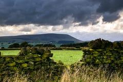 Steinwand auf dem Bauernhof mit Pendle-Hügel im Abstand am bewölkten Sommernachmittag lizenzfreie stockfotografie