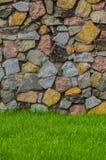 Steinwand-Beschaffenheitsfoto mit grünem Gras Stockfoto