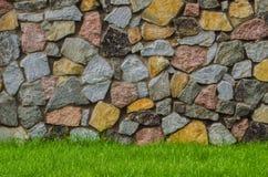 Steinwand-Beschaffenheitsfoto mit grünem Gras Lizenzfreie Stockfotografie