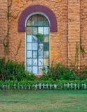 Steinwand der orangefarbenen Ziegelsteine mit dem großen alten Schmutzfenster bedeckt mit grünem Metallgitter, Boden des grünen G Stockfotografie