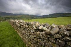 Steinwand durch landwirtschaftliches Feld Stockbilder