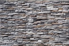 Steinwand hergestellt von gestreiften prägeartigen natürlichen Staplungsfelsen Farben sind grau weiß, schwarz, braun und Stockfoto
