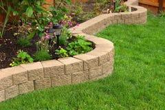 Steinwand mit dem perfekten Gras, das im Garten mit künstlichem Gras landschaftlich gestaltet lizenzfreie stockfotografie