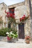 Steinwand mit Eingang und schönen Blumen Stockbild