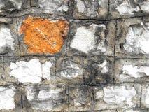 Steinwand mit Gelb auf einem Block Stockbild