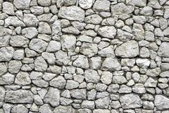 Steinwand mit gelegentlichem mit Ziegeln gedecktem Muster Lizenzfreie Stockbilder