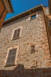 Steinwand mit geschlossenen Fenstern und Wasserspeier in der Nische an Les-Arcs-sur-Argens Lizenzfreie Stockfotos
