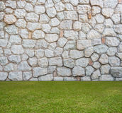 Steinwand mit grünem Feld Stockfotos