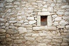 Steinwand mit kleinem Fensterbeschaffenheitshintergrund Lizenzfreies Stockfoto