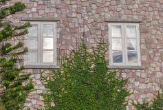 Steinwand mit kleinen Fenstern Stockfoto