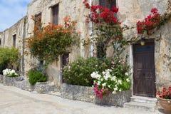 Steinwand mit Tür, Fenstern und schönen Blumen Stockfoto