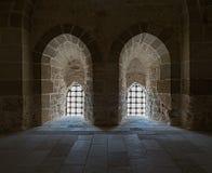 Steinwand mit zwei angrenzenden hintergrundbeleuchteten Fenstern mit Stahlgitter Lizenzfreie Stockfotos
