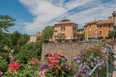 Steinwand und Häuser mit Blumen in Moustiers-Sainte-Marie Stockfotografie