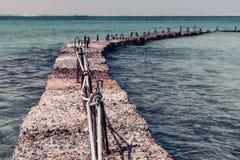 Steinwellenbrecher im Meer Stockbild