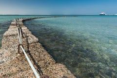 Steinwellenbrecher im Meer Stockbilder