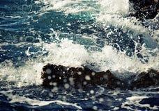 Steinwellenbrecher mit brechenden Wellen. Lizenzfreies Stockfoto