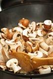 Steka champinjoner i en woka Arkivbilder