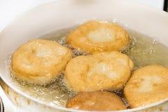 Steka donuts i varm olja Hemlagade inhemska donuts som förbereder sig i varm olja Fotografering för Bildbyråer